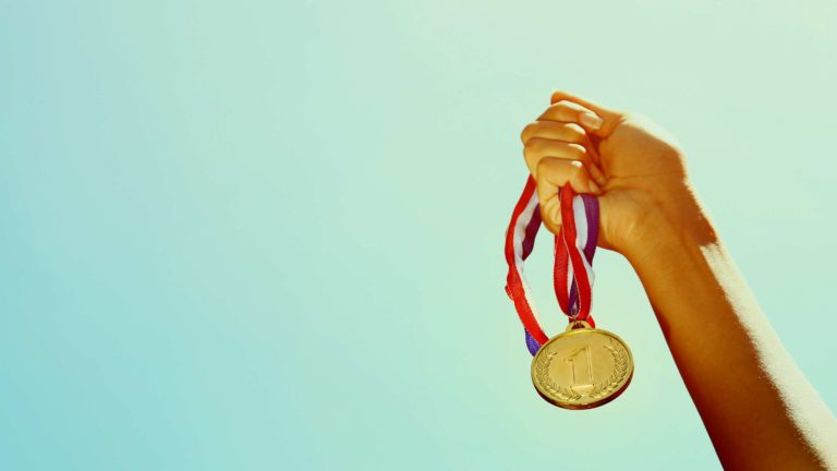 Decision Science | Arts & Culture Fundraising | Hand holding an Olympic gold metal - slide